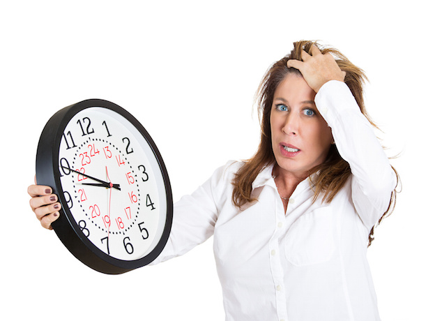 Business woman running out of time, holding wall clock